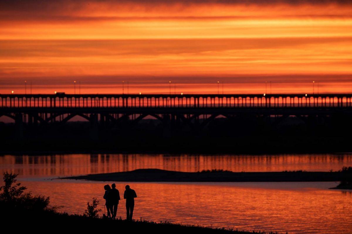 The sun sets as a family walks along the Volga river, next to the Nizhny Novgorod Stadium in Nizhny Novgorod, Russia, on June 26, 2018.