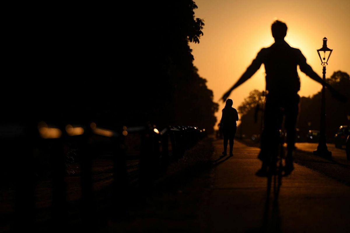A woman walks in front of a cyclist with his arms outstretched during sunset in Dublin, Ireland, on June 27, 2018.