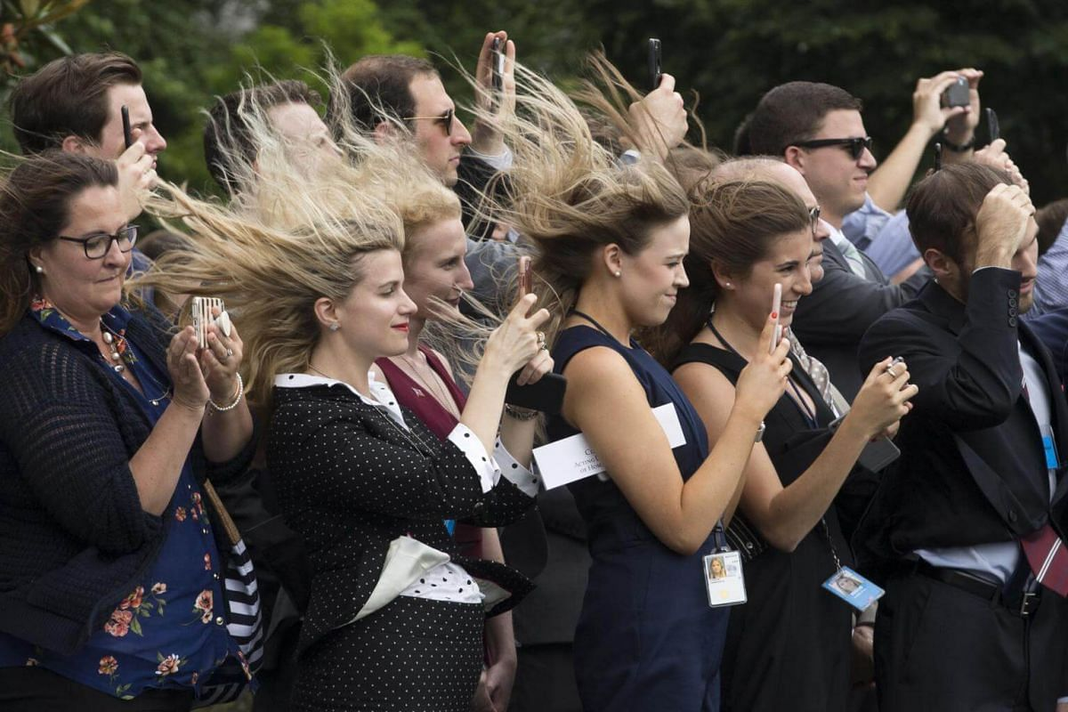 Wind created by Marine One taking off blows through the hair of visitors on the South Lawn as they watch the departure of US President Donald Trump, in Washington, DC, on June 27 2018.