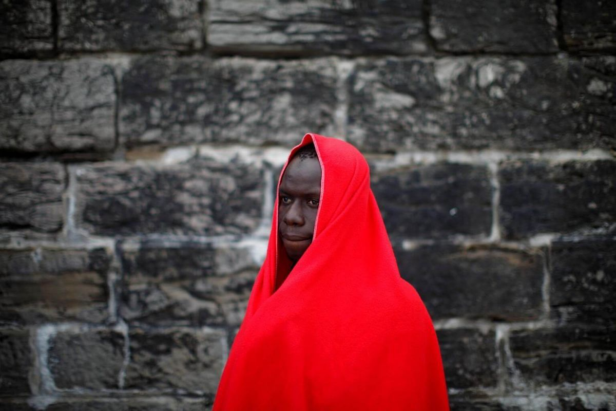 A migrant of a group intercepted aboard a dinghy off the coast in the Strait of Gibraltar, stands after arriving on a rescue boat at the port of Tarifa, southern Spain, on June 27, 2018.