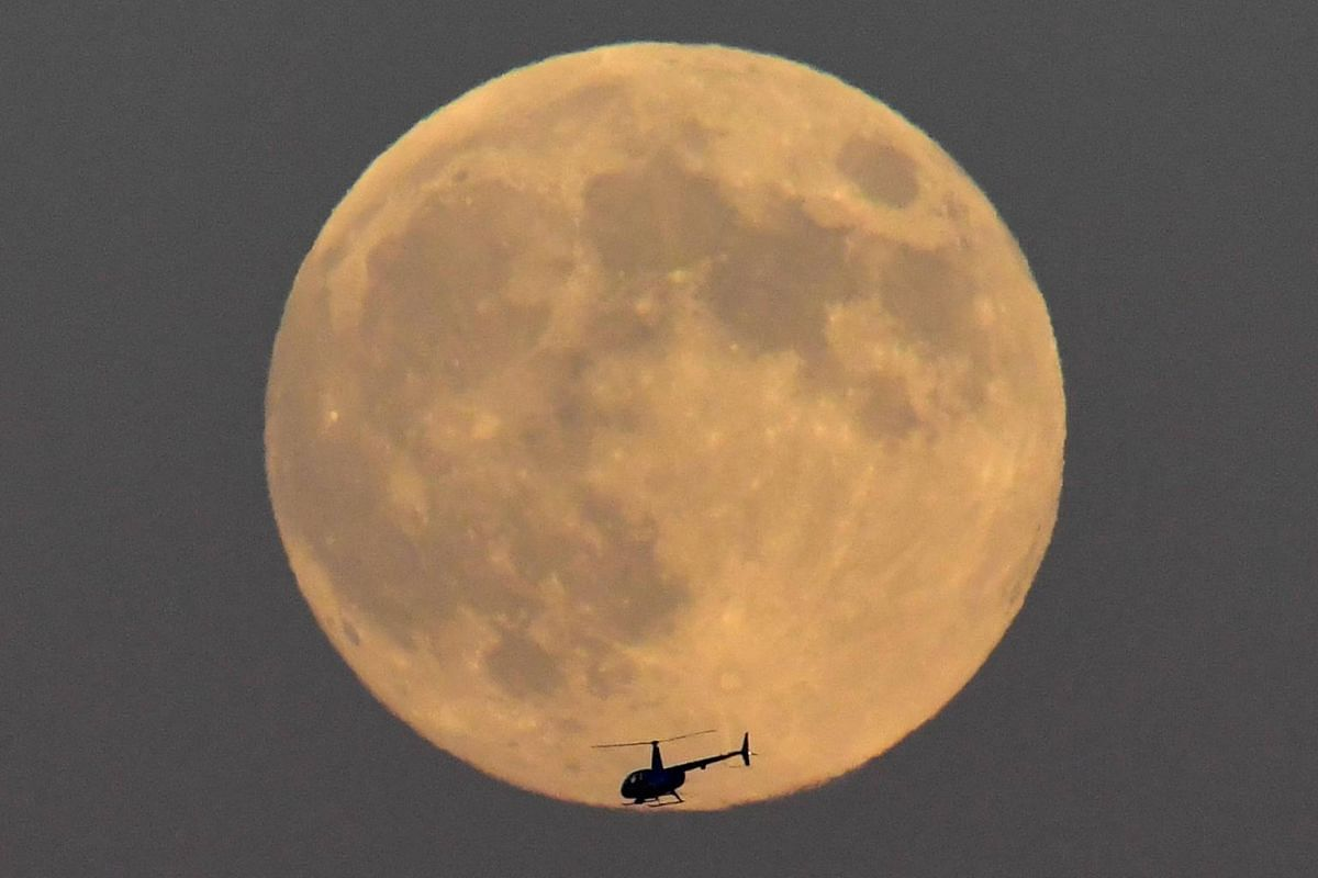 A helicopter is seen passing in front of the moon, typically called a 'Strawberry Moon' when full in June, above London, Britain, on June 27, 2018.