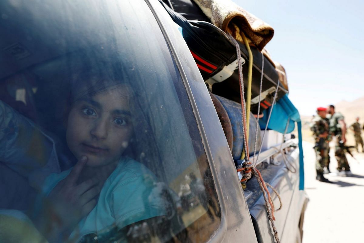 A Syrian refugee girl who left Lebanon looks through a window as she arrives in Qalamoun, Syria, on June 28, 2018.