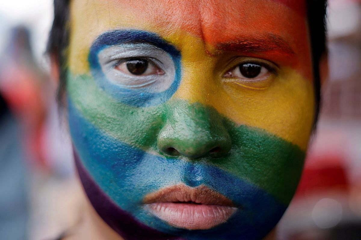 An activist, with his face painted in the colours of the rainbow flag, participating in a march organized by the LGBT community in Managua, Nicaragua.