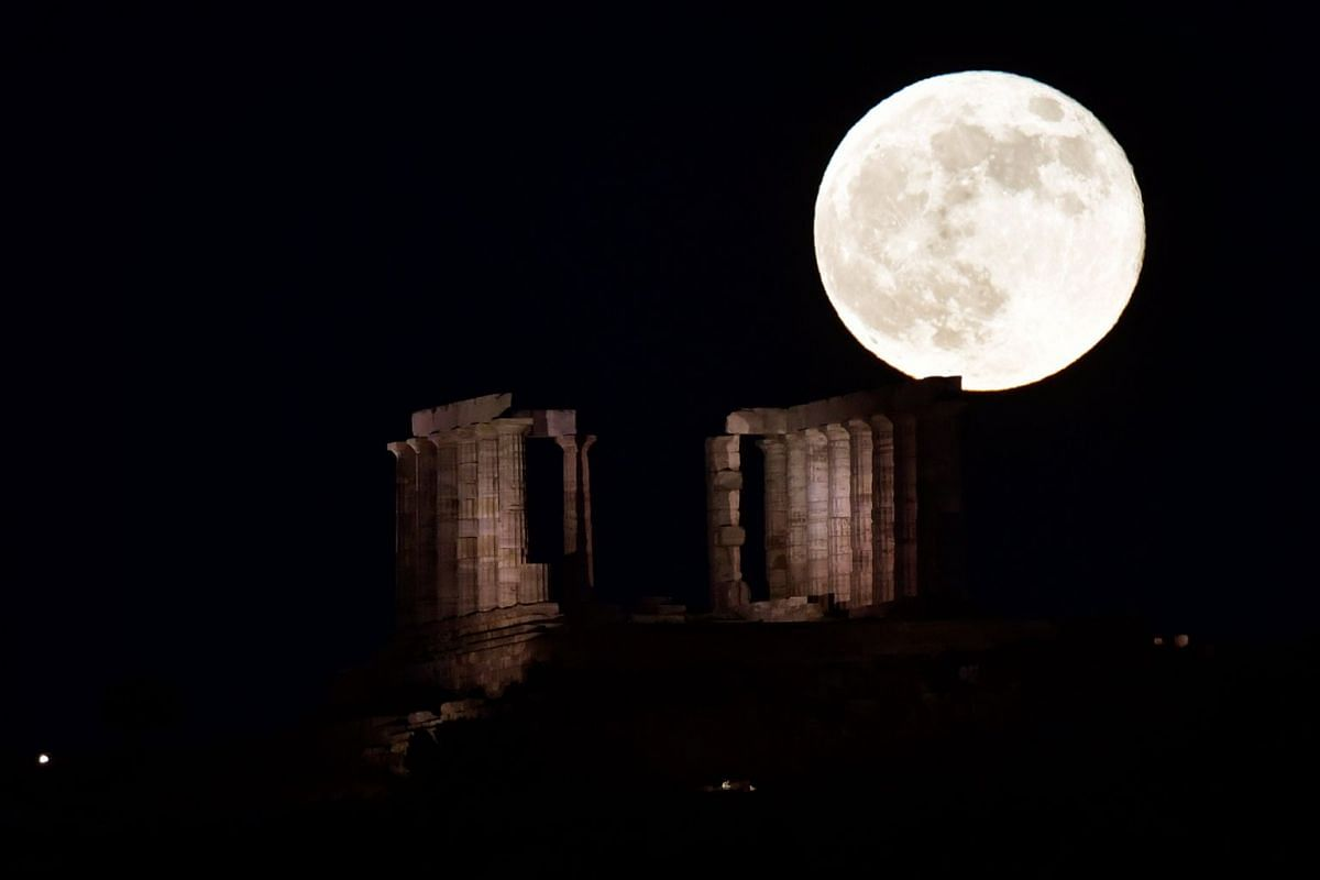 A full moon rises behind the Temple of Poseidon in Sounion, some 70 km south of Athens, Greece, on June 28, 2018.