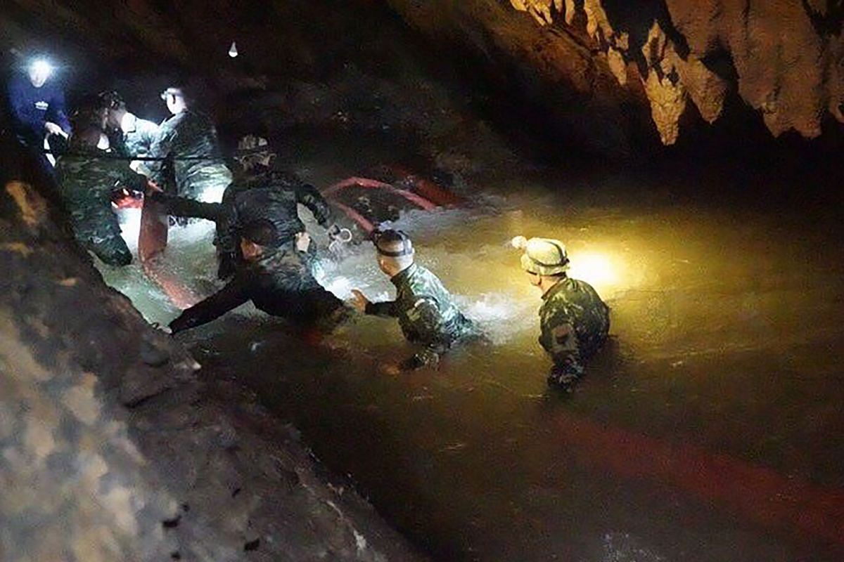 Top: A team of Seal divers from the Thai navy looking for the missing boys in the water-filled tunnel in the Tham Luang cave on Friday.