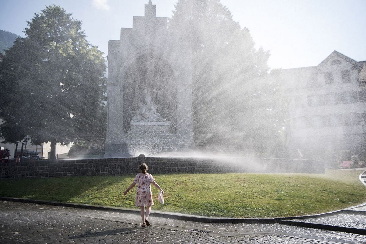 A woman enjoys the cool splash of water in front of the Winkelried Memorial on the village square in Stans on the occasion of Stans' 125th anniversary celebrations of the water supply in Stans, Switzerland, July 01, 2018.