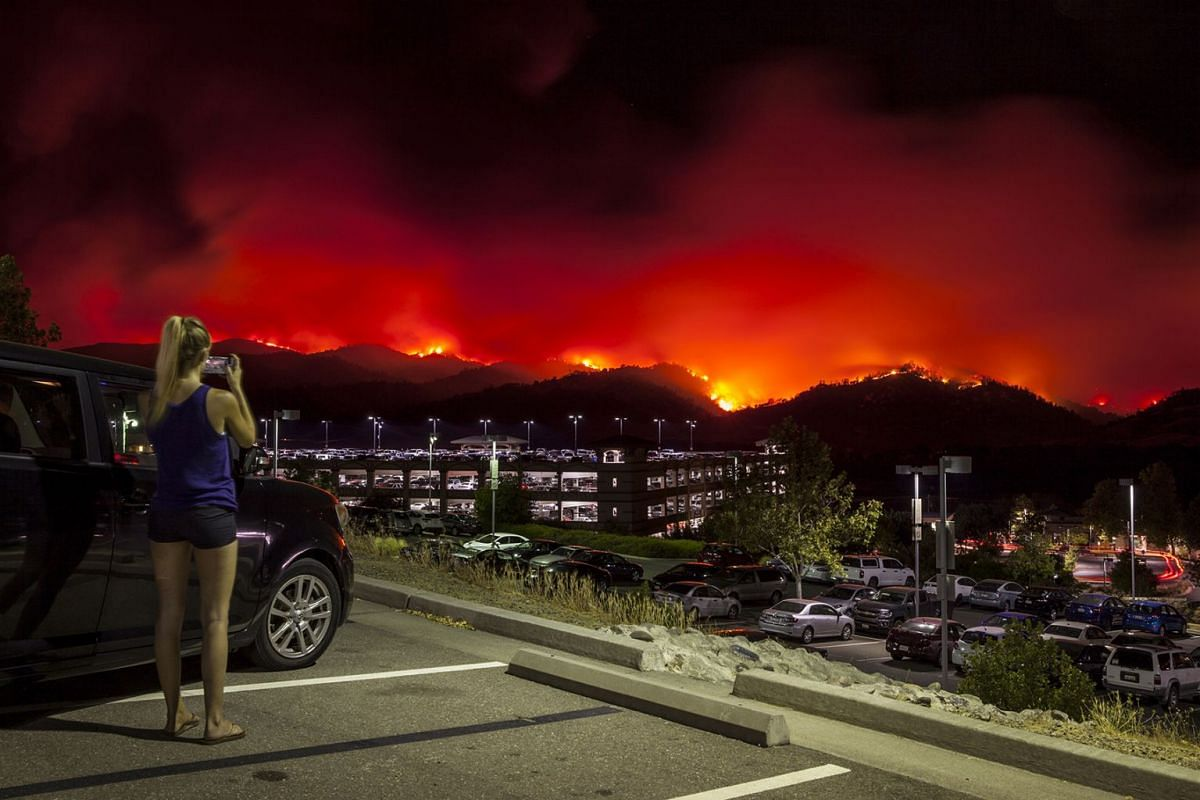 A local resident takes pictures from the upper parking lot of the Cache Creek Casino Resort over looking the County Fire as it burns out of control in Brooks, California, USA, June 30, 2018. Fire is being driven by red flag weather conditions, consis