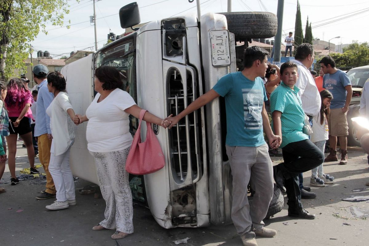 Mexican citizens guard a vehicle that overturned while fleeing with stolen ballots in Puebla, Mexico, July 01, 2018. Mexicans go to the polls to choose 3,400 public officials including the president of the country, 128 senators, 500 deputies, eight g
