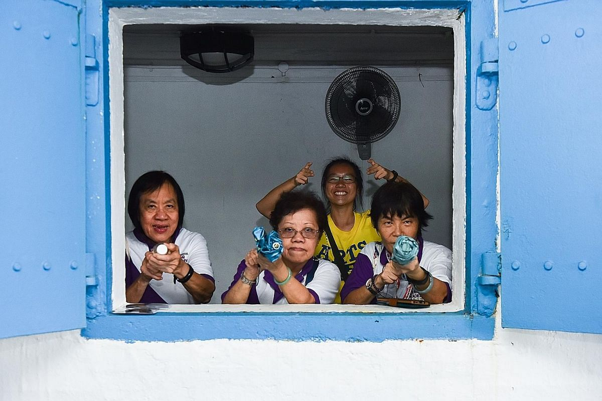 (From left) Madam Linda Lim Sor Bee, 70, Madam Tan Quee Choo, 66, Ms Klara Ong Jing Hui, 21, and Madam Chow Li Chin, 64, posing for a fun shot while waiting out the rain at Fort Siloso. By the second day, there were no signs of shyness between the se