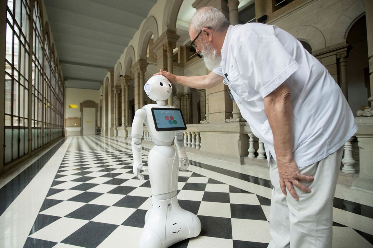 Spanish director Joan Escarrabell touches Pepper the robot during its presentation as Clinic Hospital in Barcelona, Spain, 02 July 2018. Pepper can talk with patients in 21 languages, it detects if they are sad or happy or amuses them with music and