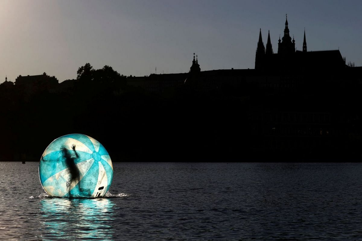 A girl plays inside a giant plastic ball, called Zorb on the Vltava River in Prague, Czech Republic, July 2, 2018.