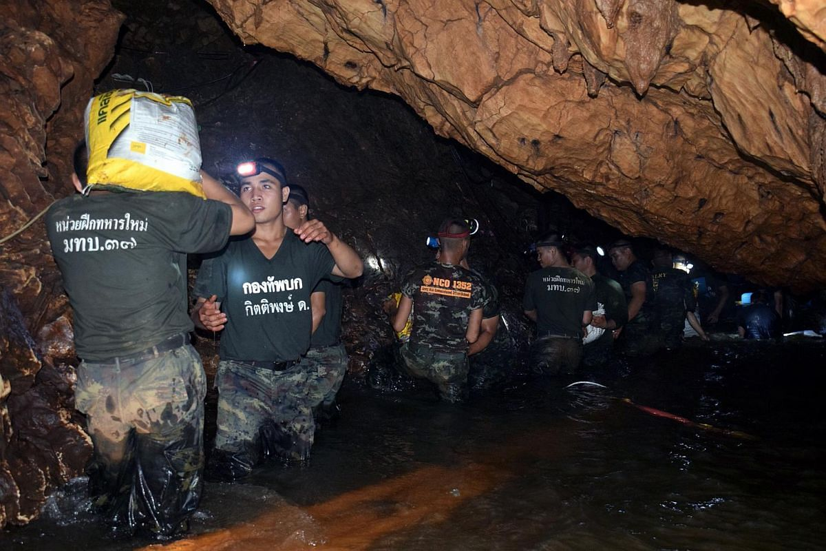 A photo released by Royal Thai Army on July 2, 2018, shows Thai soldiers carrying equipment inside a flooded cave complex during a rescue operation for the missing soccer team and their coach at Tham Luang cave in Khun Nam Nang Non Forest Park, Chian