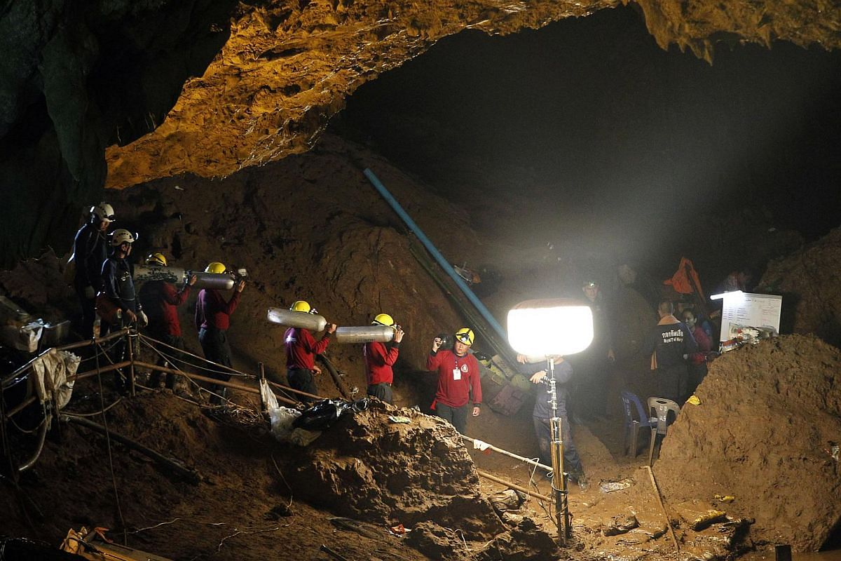 Thai officials carrying oxygen tanks through a cave complex during a rescue operation for the missing football team at the Tham Luang cave in Khun Nam Nang Noon Forest Park in Chiang Rai province, Thailand, on June 30, 2018.