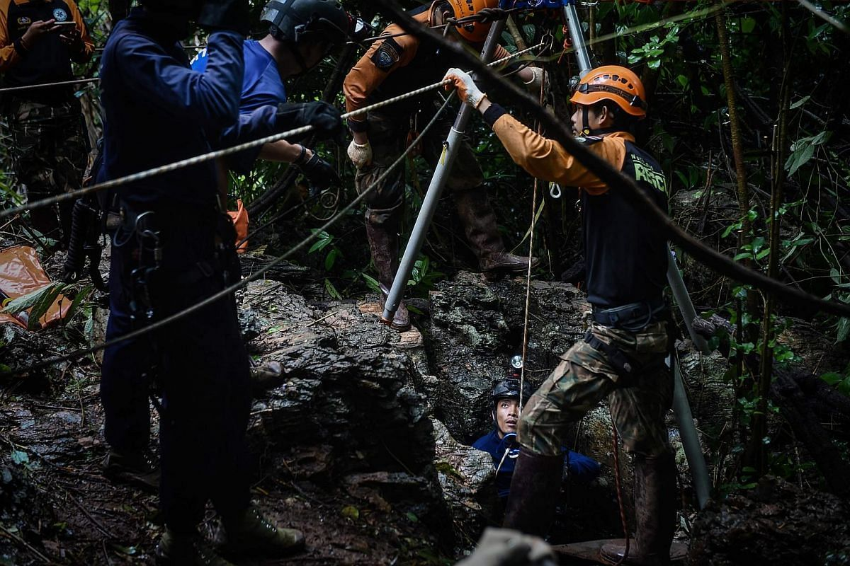 Thai rescue specialists (in orange) help a Thai Airforce soldier down a possible opening to the Tham Luang cave, at the Khun Nam Nang Non Forest Park in Chiang Rai province, on June 30, 2018.