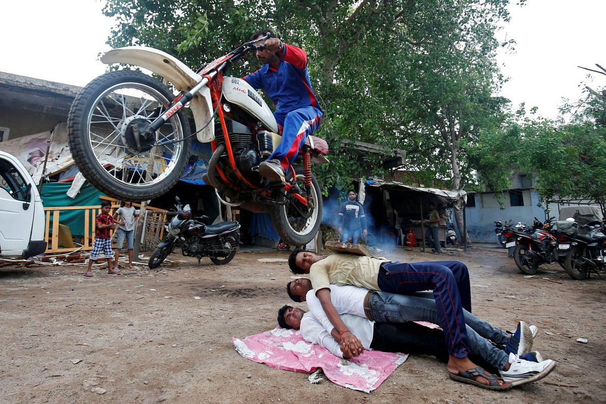 A Hindu devotee performing a stunt with his motorcycle during his rehearsals for the annual Rath Yatra, or chariot procession, in Ahmedabad, India, on July 3, 2018.