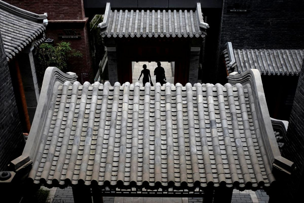People walking through a traditional gate at the new business center, Beijing Fun, in Beijing's Qianmen area, China, on July 3, 2018.
