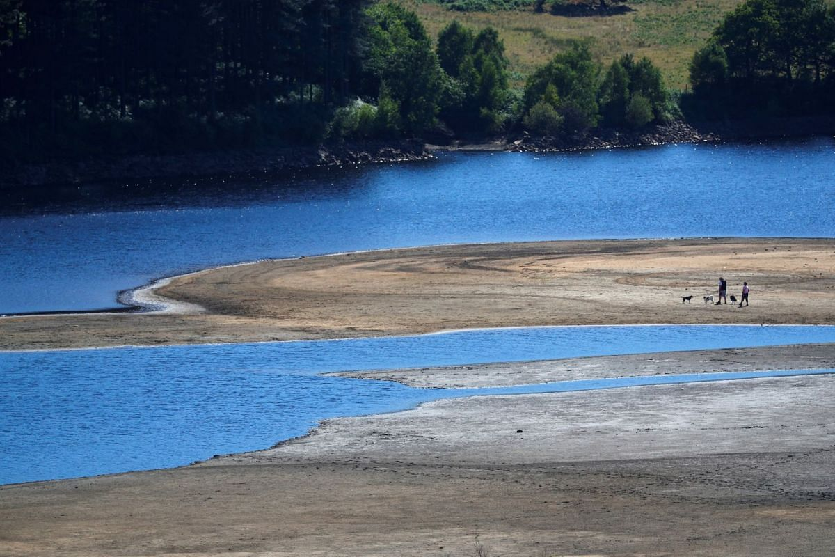 Two people take a walk near the water's edge of Torside Reservoir in Derbyshire, where the water level has dropped significantly thanks to the UK heatwave.