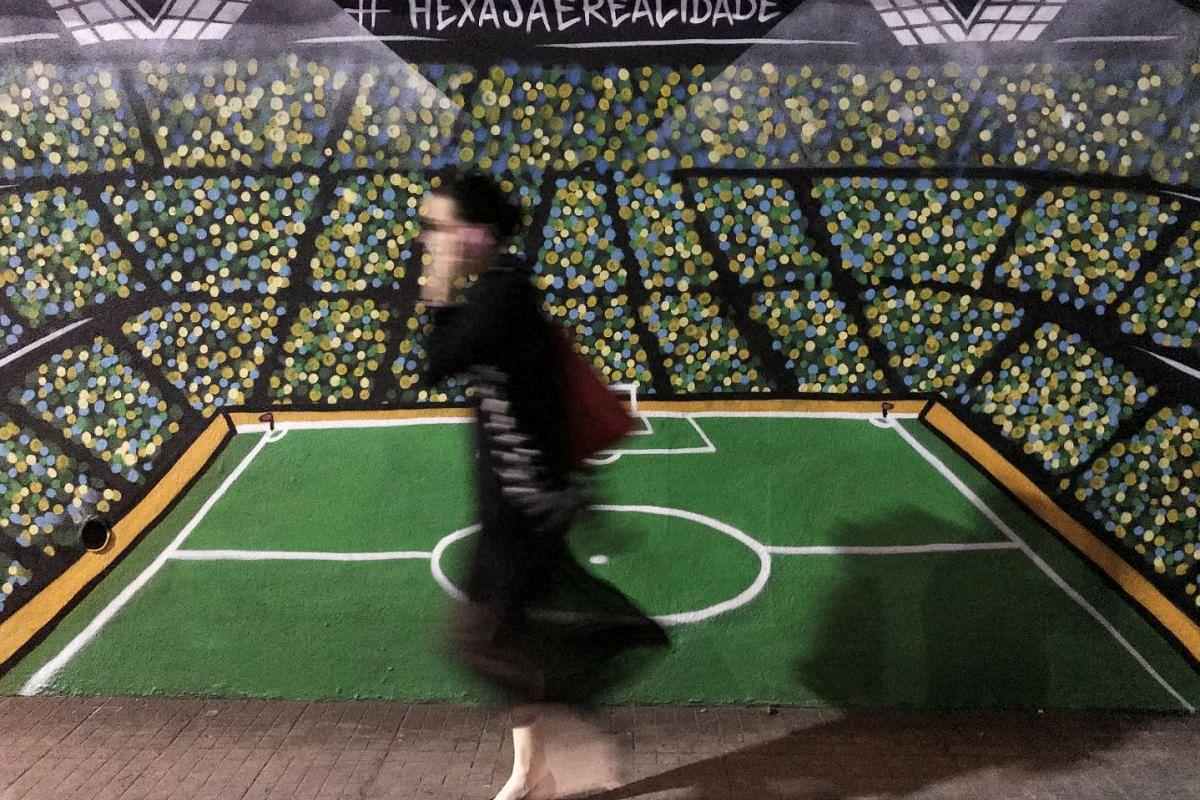 A woman walking past a football field painting along a street in Sao Paulo, Brazil, on July 3, 2018.