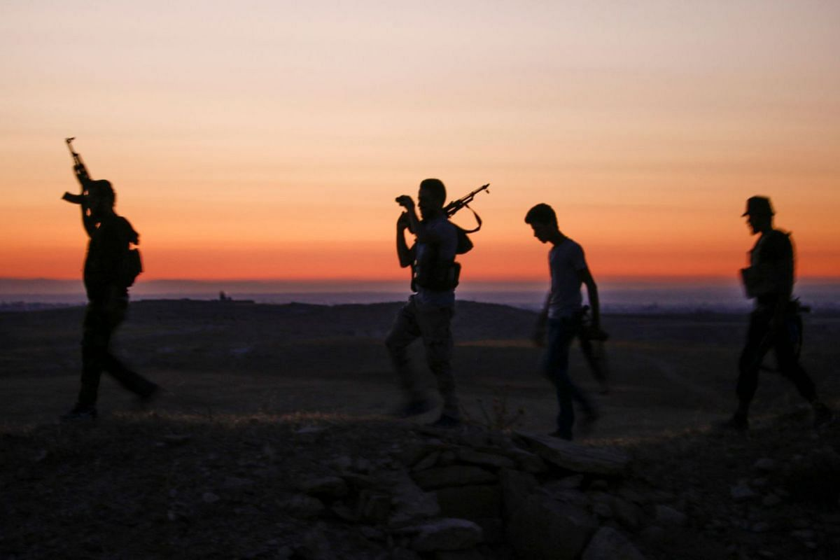 Syrian rebel fighters walking with their arms near the frontline against government forces west of the embattled southern city of Daraa, Syria, on July 3, 2018.