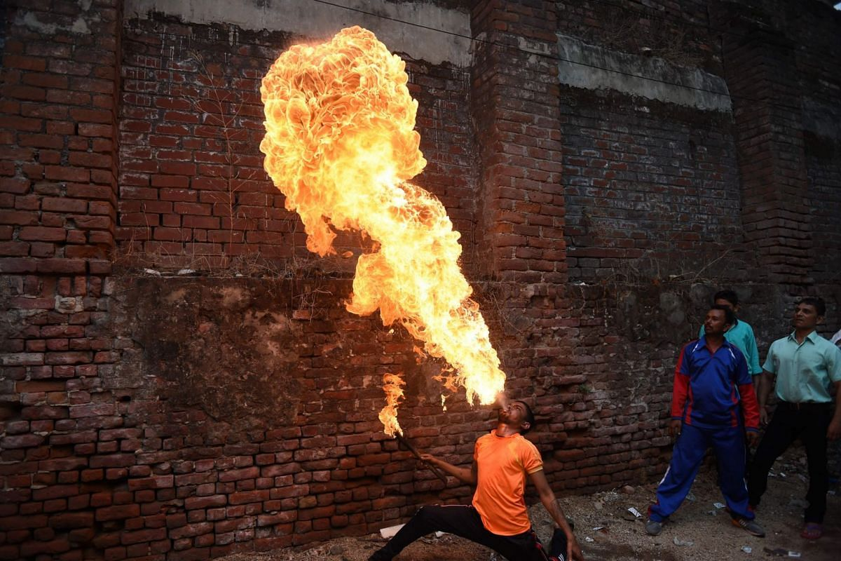 Vikas Dataniya, Indian stuntman, releases flames from his mouth as he rehearses ahead for the annual Rath Yatra (Chariot Procession) of Lord Jagannath in Ahmedabad, on July 3, 2018.