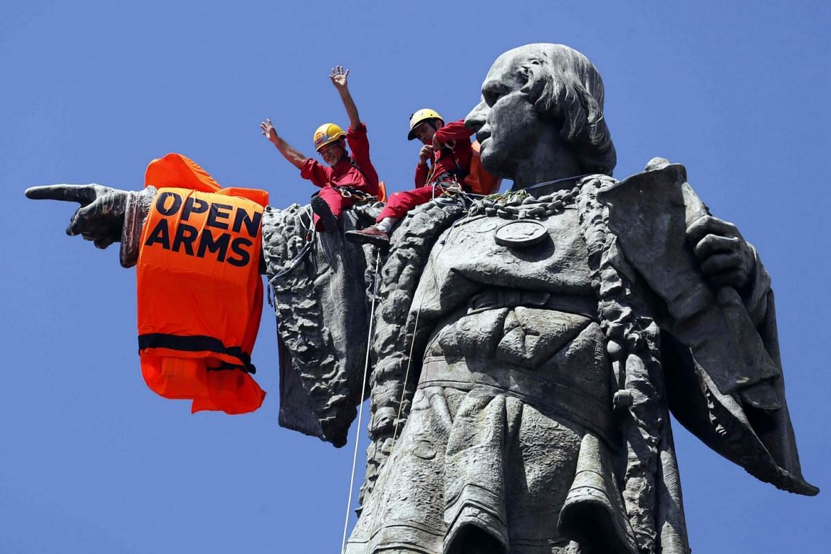 Activists place a lifejacket on the arm of Columbus monument in Barcelona as the rescue vessel Open Arms arrives to the city, in Spain, on July 4, 2018.