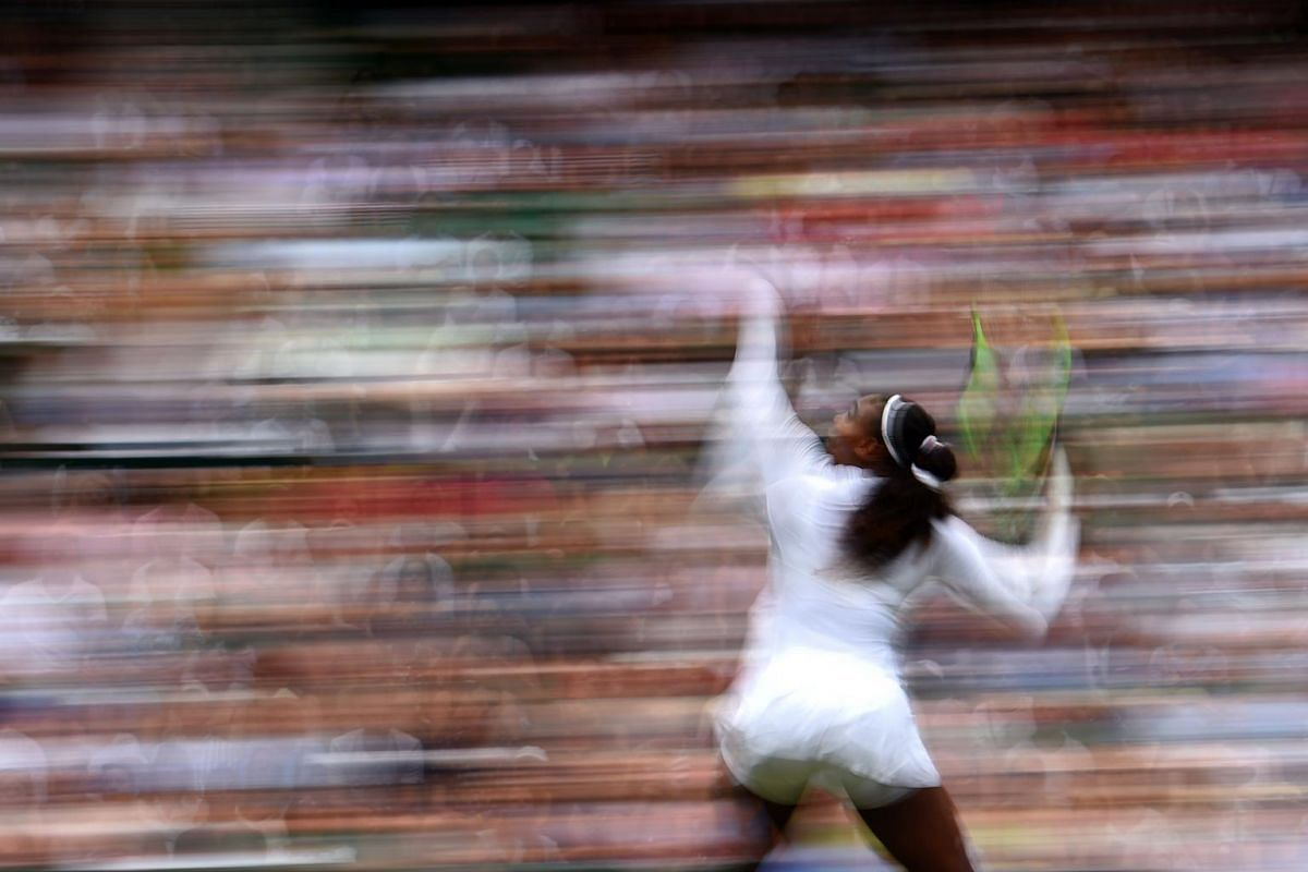 Serena Williams throws the ball to serve during her women's singles second round match on the third day of the 2018 Wimbledon Championships at The All England Lawn Tennis Club in Wimbledon, on July 4, 2018.