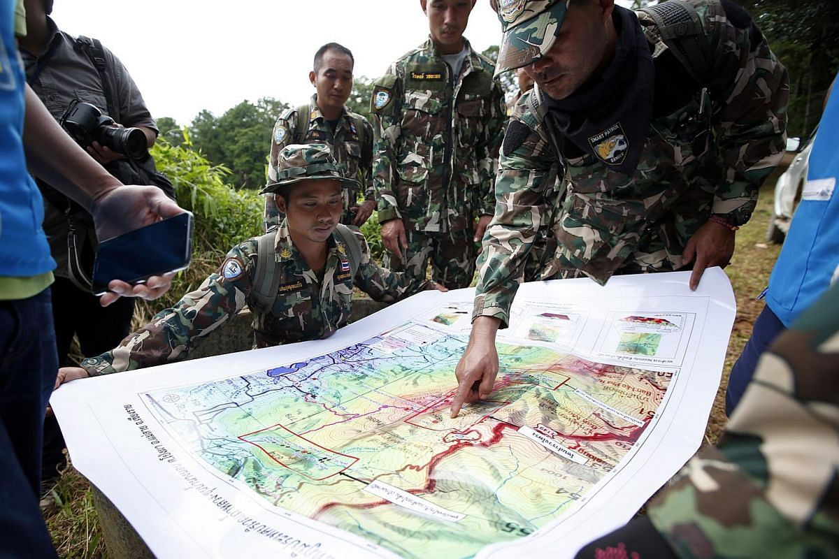 Thai forest rangers examining a map while looking for potential drilling options to rescue the boys on July 7, 2018.
