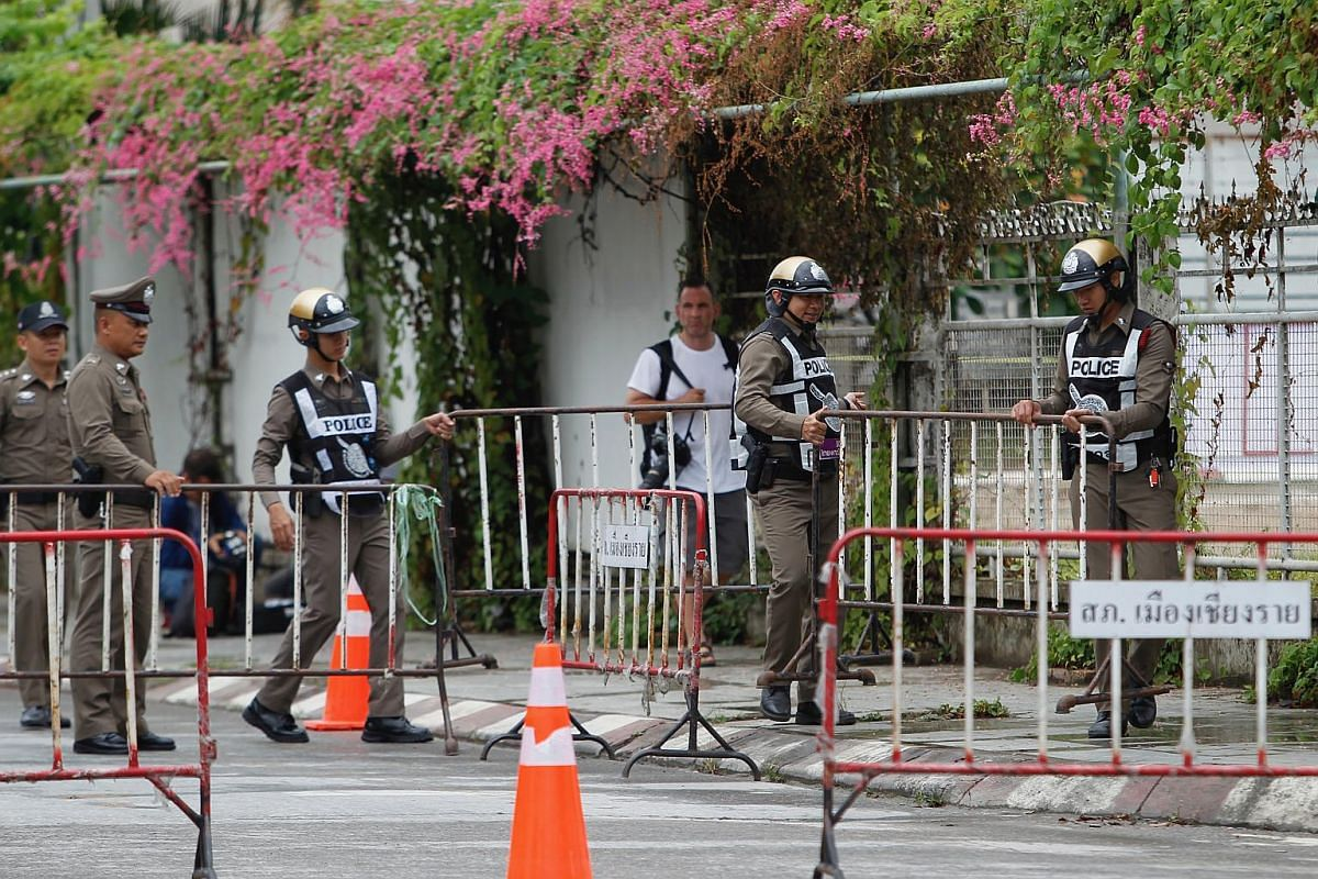 Thai police officers setting up barricades along the road outside the hospital in Chiang Rai province, in preparation for the arrival of the youth football team, on July 8, 2018.
