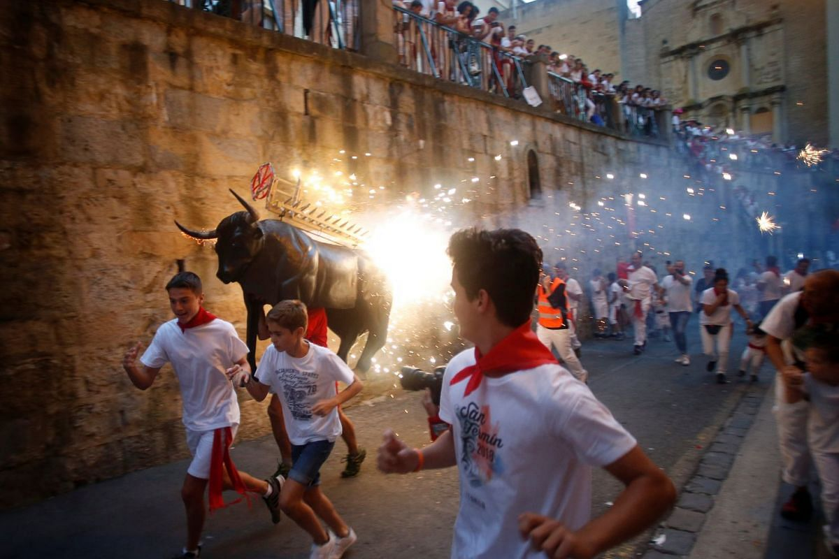 Revellers run from the Fire Bull, a man carrying a bull figure packed with fireworks, at the San Fermin festival in Pamplona, Spain July 8, 2018.