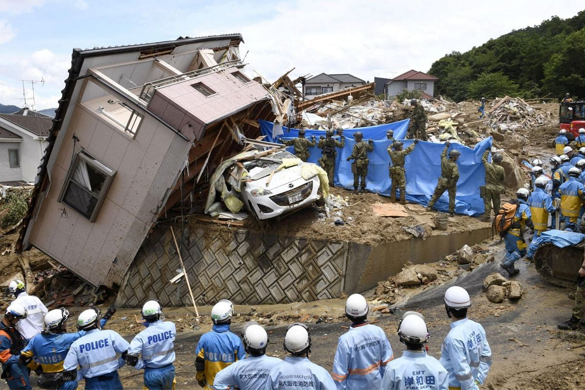Rescue workers look for missing people in a house damaged by heavy rain in Kumano town, Hiroshima Prefecture, Japan, July 9, 2018.