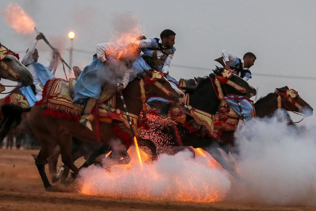 "Horsemen ride in a choreographed cavalry charge in a fantasia during the 14th Tan-Tan Moussem Berber festival on July 8, 2018 in the western Moroccan desert town of Tan-Tan. The festival, which is recognised by UNESCO as a ""Masterpiece of the Oral an"