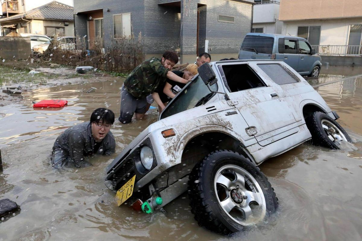Residents try to rescue a submerged car in the area of Kurashiki, Okayama Prefecture, Japan, on July 9, 2018.