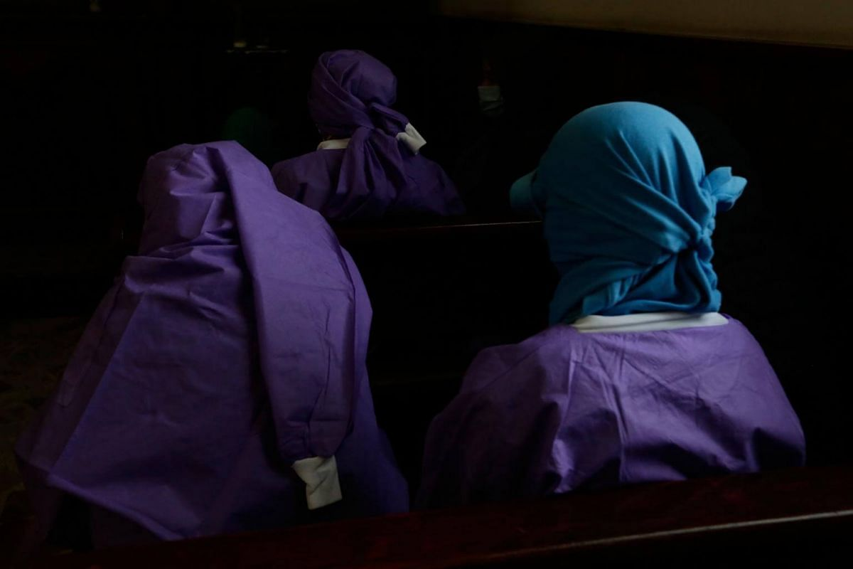 Women afraid of pro-government Sandinista youths cover themselves as they take shelter at the San Sebastian Basilica in Diriamba, Nicaragua, on July 9, 2018.