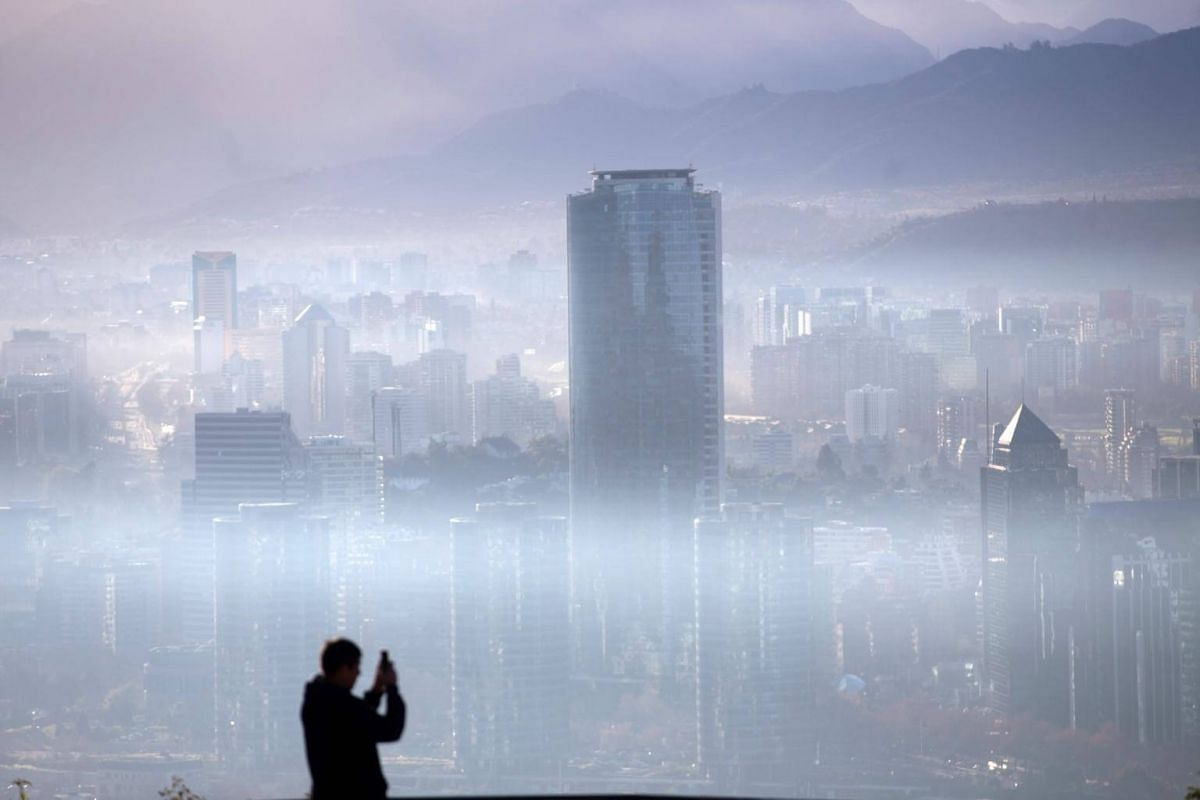 A person takes a picture of the smog over Santiago, Chile, on July 9, 2018.