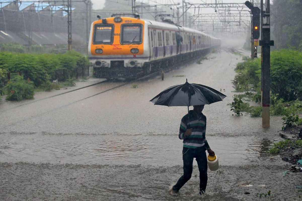 A man carrying an umbrella walks past a passenger train that moves through a water-logged track during heavy rains in Mumbai, on July 9, 2018.