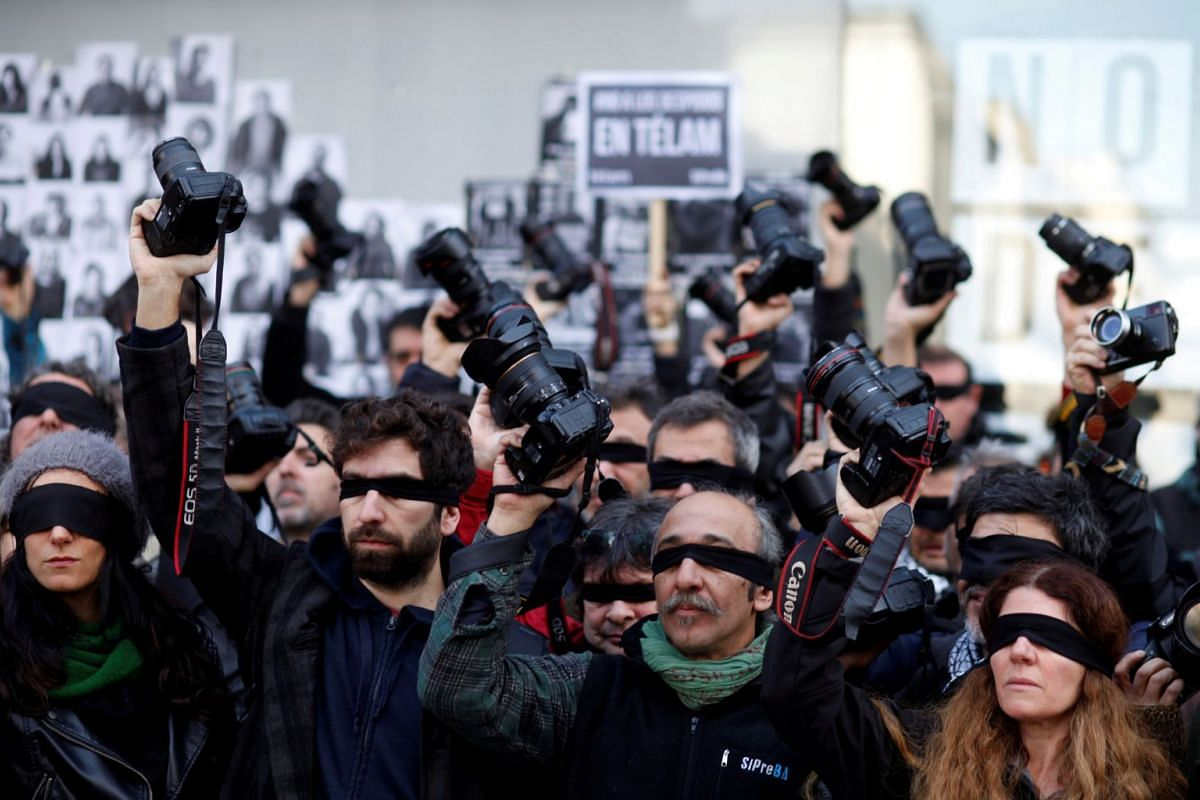 Blindfolded Argentine journalists hold up cameras during a protest against the layoff of over 300 employees from the public news agency Telam in Buenos Aires, Argentina, July 11, 2018.