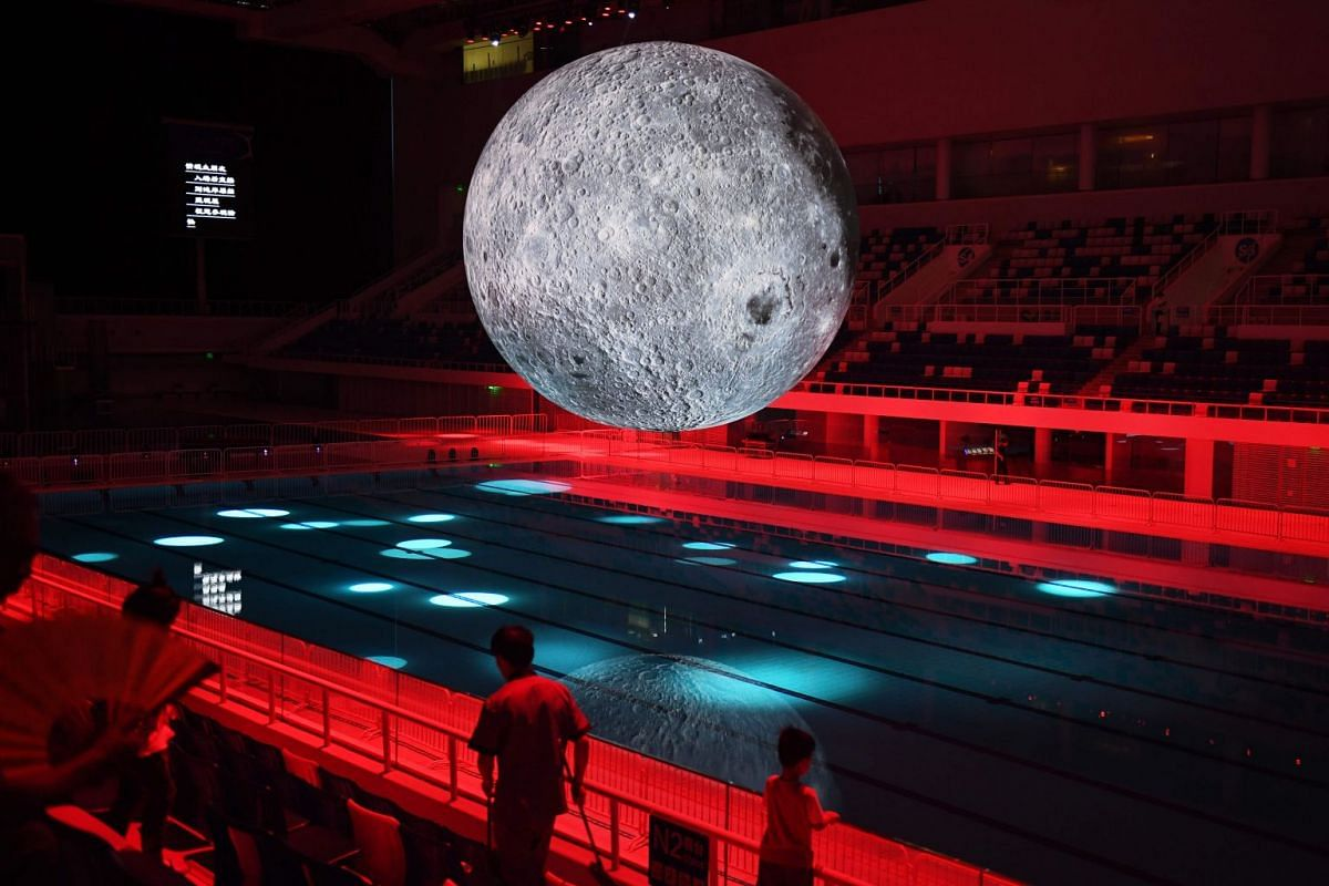 A model of the moon hangs above the Olympic swimming pool at the National Aquatics Center, known as the Water Cube, in Beijing on July 11, 2018. The moon model is part of an exhibition about China's moon exploration technology and achievements. China