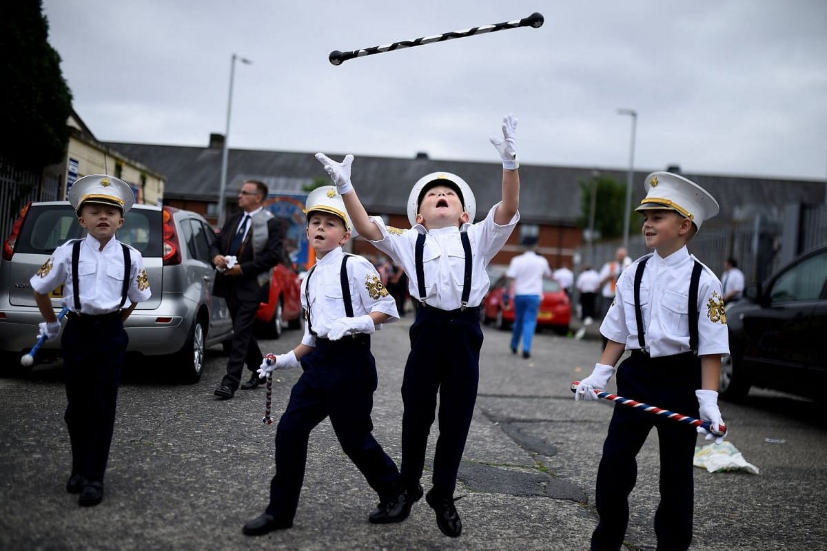 Young members of Loyalist Orders throw a baton in the air as they participate in Twelfth of July celebrations in Belfast, Northern Ireland, July 12, 2018.