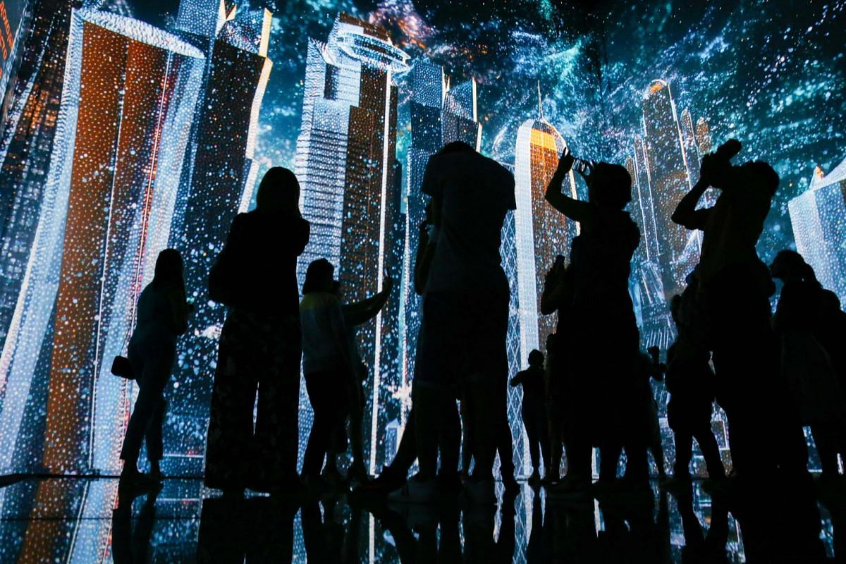 People watch a light show at the multimedia museum 'Qatar Elements' during an exhibition devoted to the future world championships in Qatar in 2022, at the Gorky Parc in Moscow, on July 12, 2018. Qatar will host the FIFA World Cup in 2022.