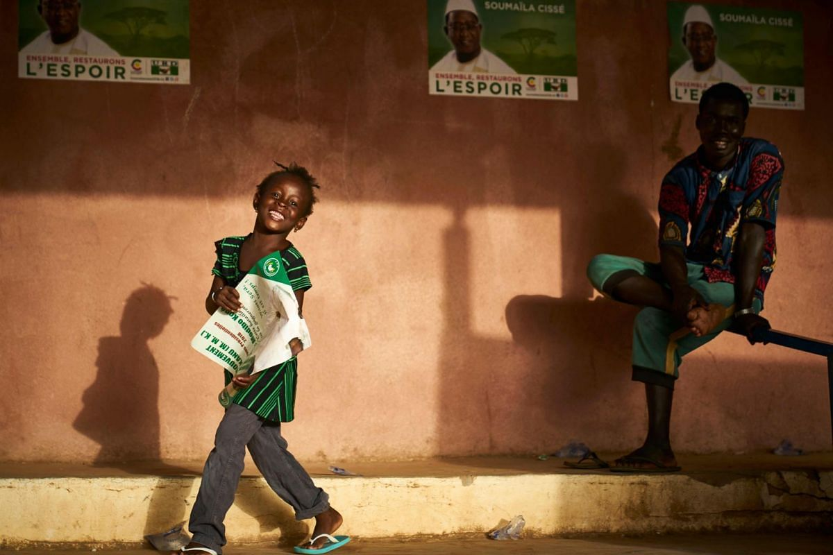 A young girl holds a poster for Malian opposition candidate for the presidential elections Soumaila Cisse during a rally in Koulikoro on July 12, 2018. Mali's incumbent president Ibrahima Boubacar Keita, who took office in 2013, and opposition frontr