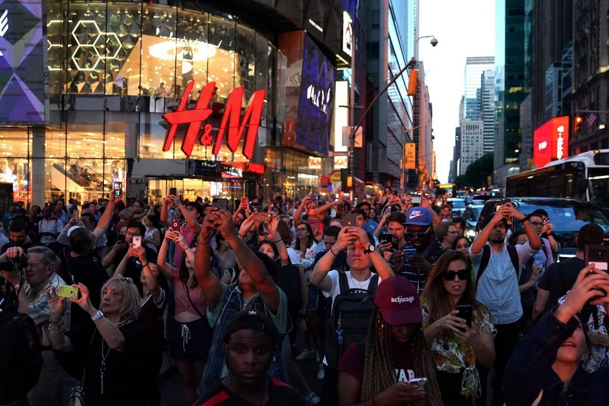 People take photos with their mobile phones as the sun sets as seen from 42nd street in Times Square in New York City on July 12, 2018 during Manhattanhenge. Sometimes also referred to as Manhattan Solstice, Manhattanhenge is a biannual natural event