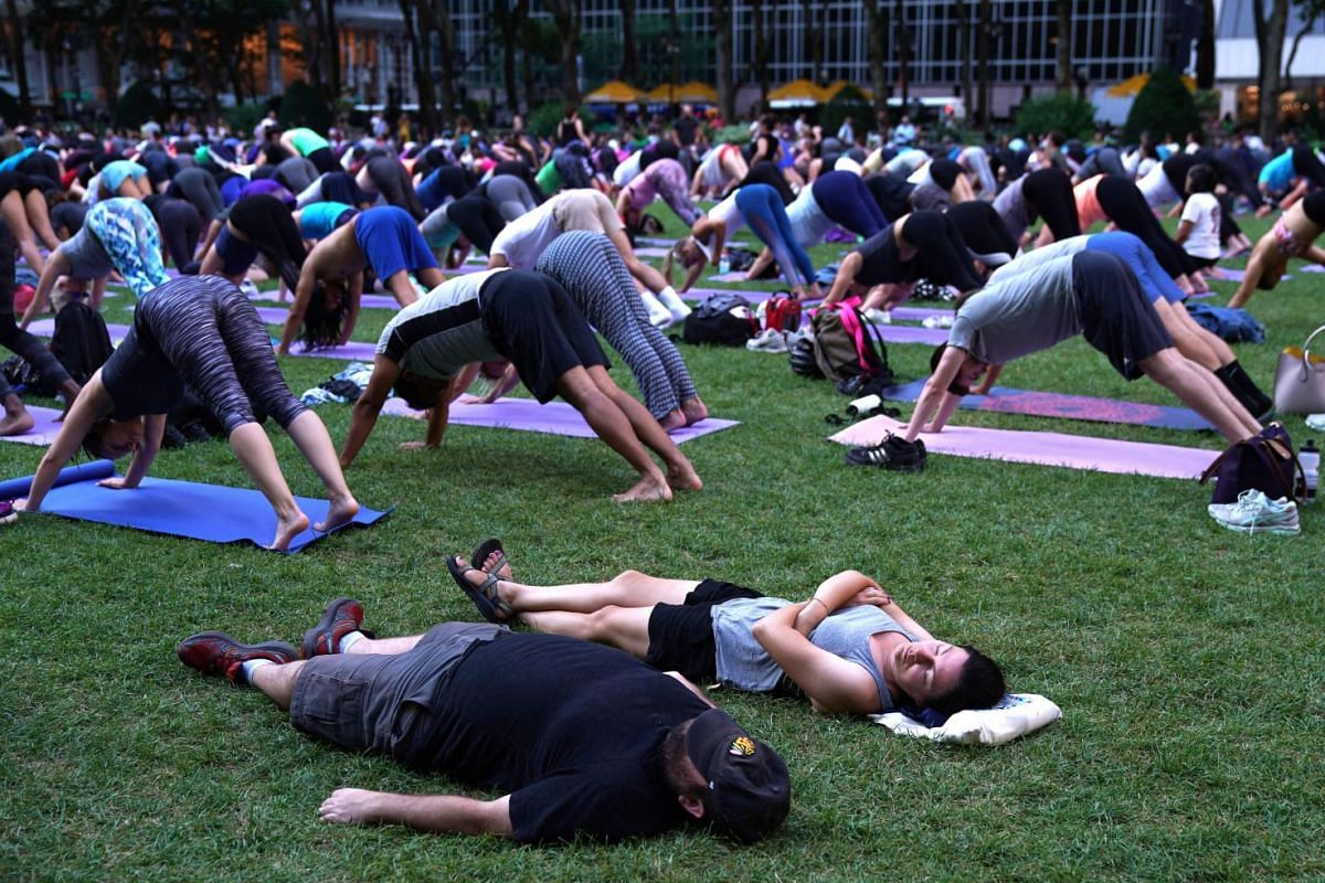 A couple of tourists nap in the grass as people participate in an outdoor yoga event in Bryant Park in New York City July 12, 2018.