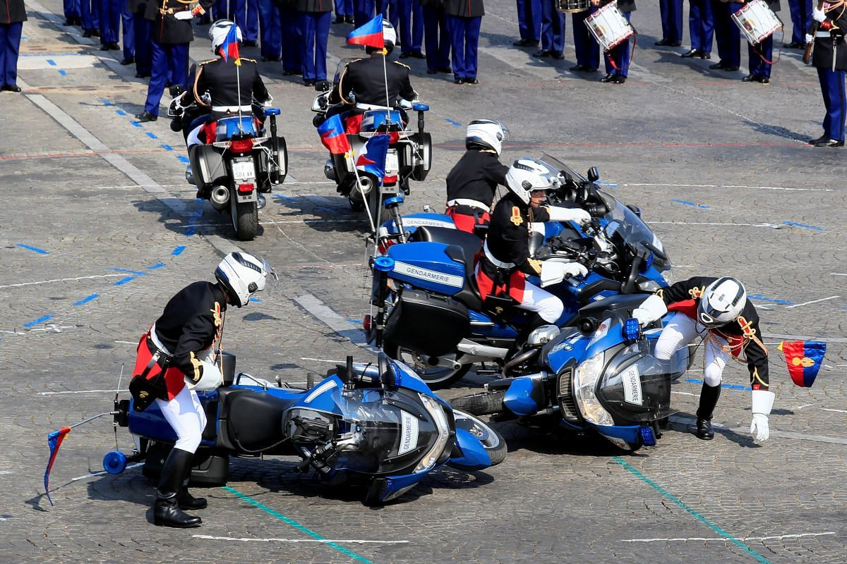 French gendarmes right their motorcycles after a fall during the traditional Bastille Day military parade on the Champs-Elysees Avenue in Paris on July 14, 2018.