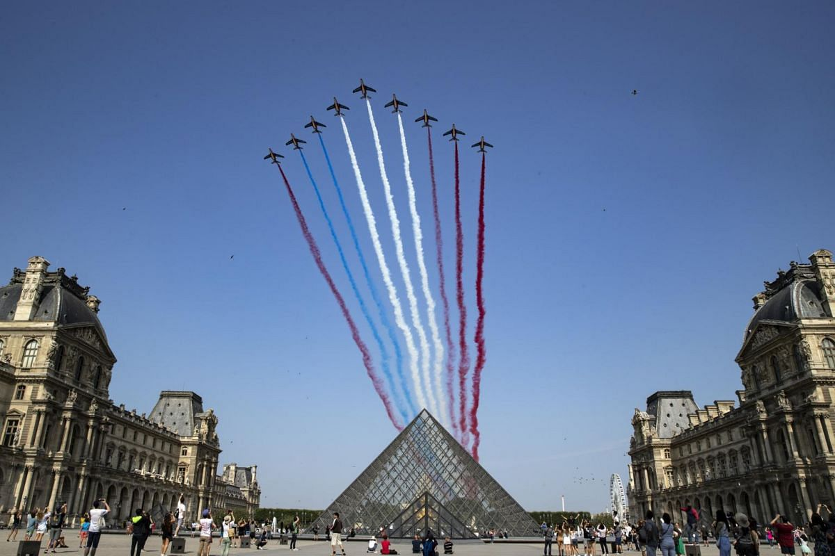 The Patrouille de France alphajets  pass over the Louvre Museum during Bastille Day celebrations in Paris on July 14, 2018.