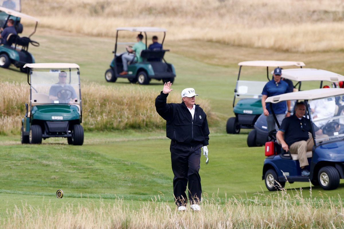US President Donald Trump waves as he walks on the golf course of the Trump Turnberry in Ayrshire, Scotland, on July 14, 2018.