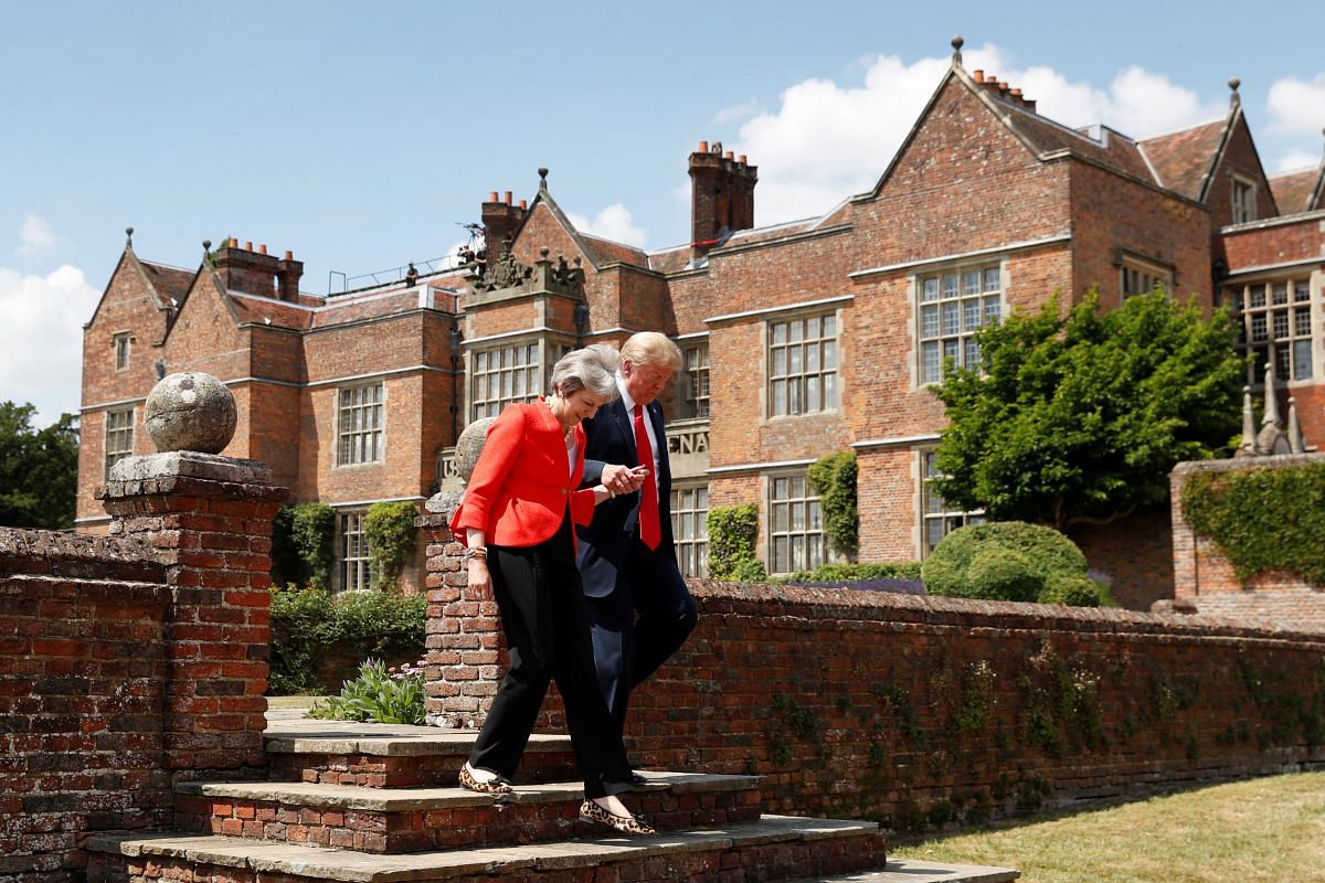 Britain's Prime Minister Theresa May and US President Donald Trump arrive for a press conference at Chequers, the official country residence of the Prime Minister, on July 13, 2018.
