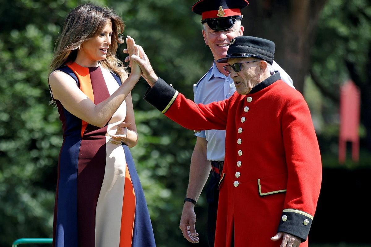 """US First Lady Melania Trump high-fives with a British military veteran known as a """"Chelsea Pensioner"""" during a game of bowls at The Royal Hospital Chelsea in London on July 13, 2018."""