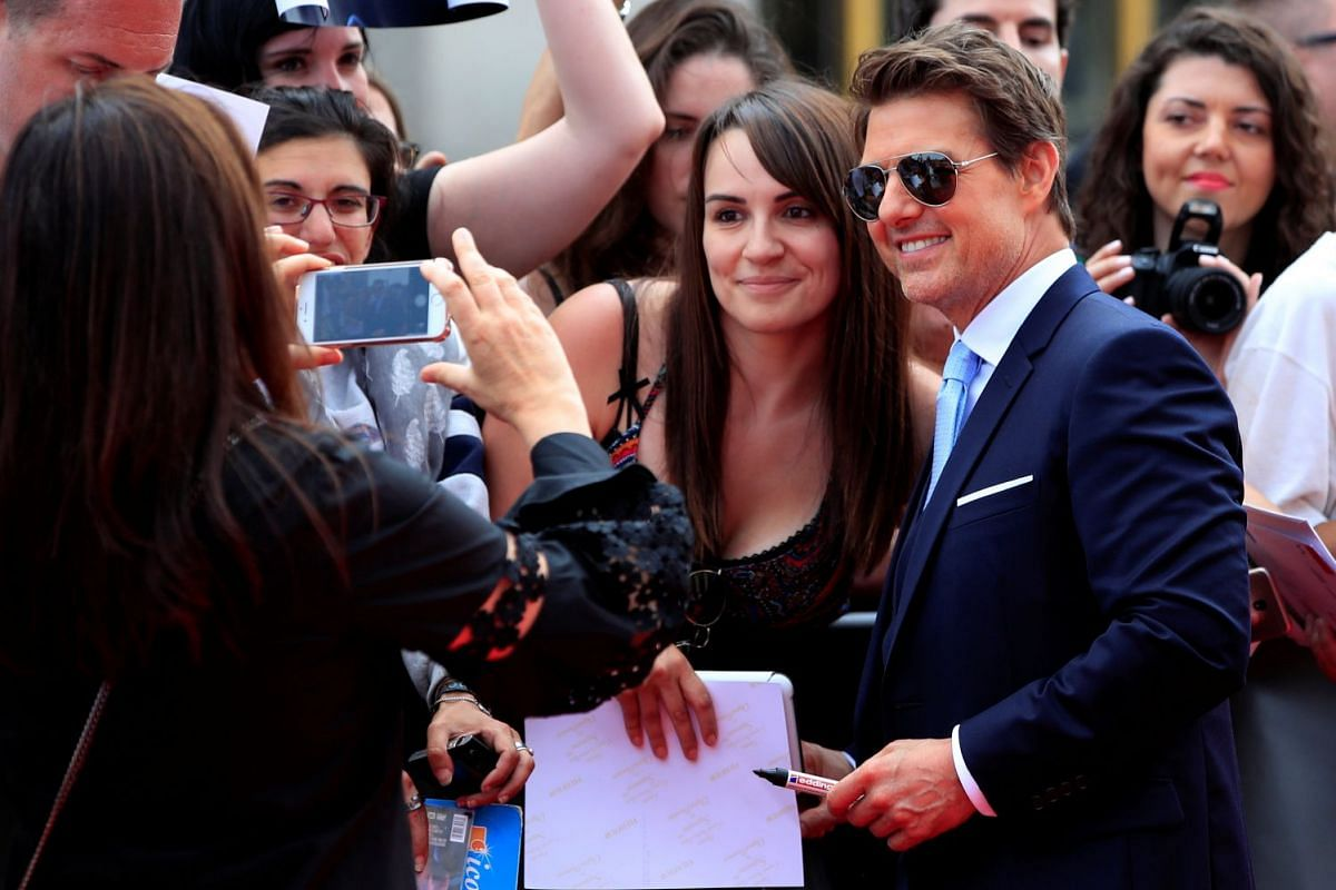 Tom Cruise posing for a picture with a fan as he arrives for the movie premiere in Paris.
