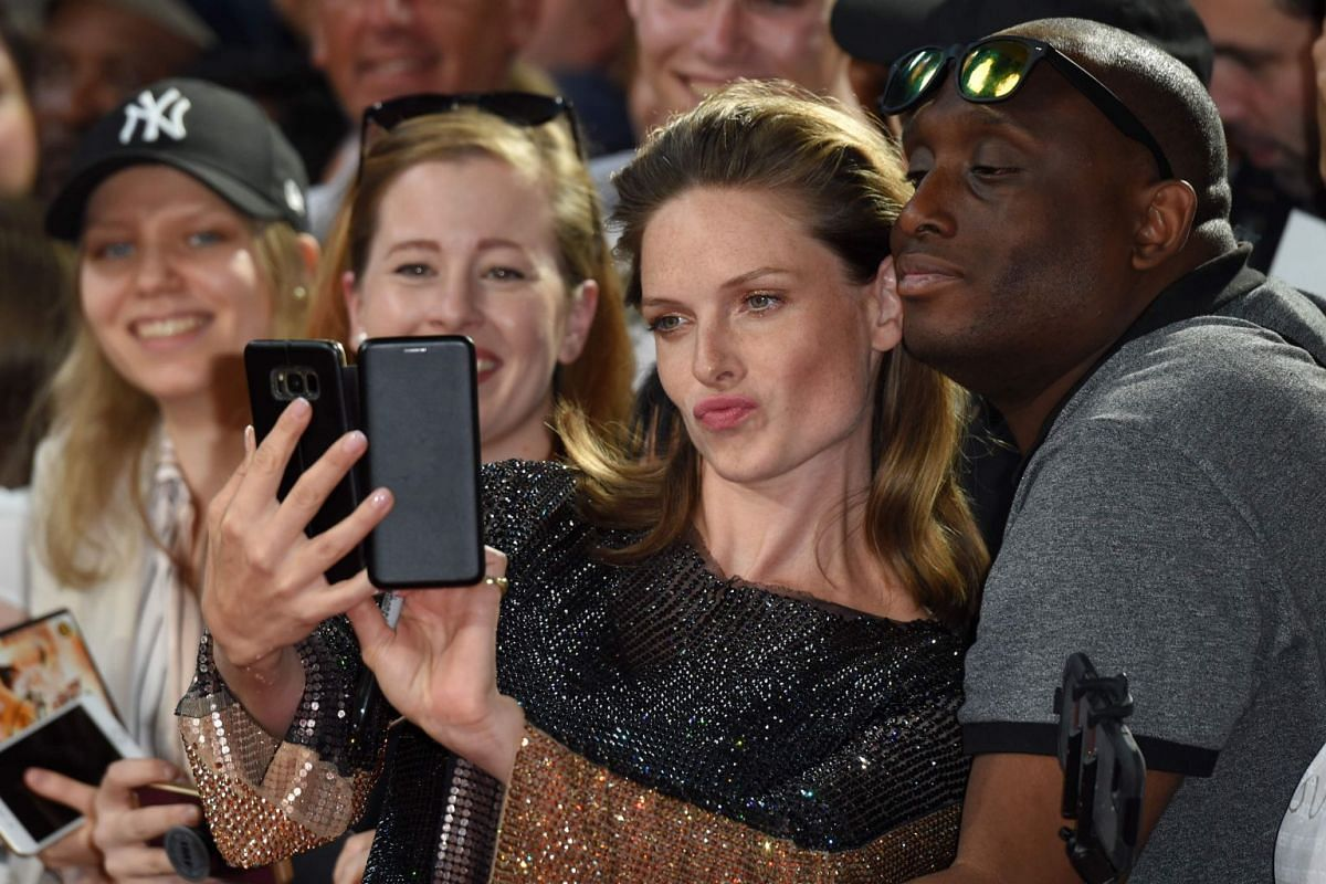 Actress Rebecca Ferguson posing for a selfie with fans on the red carpet in London on July 13, 2018.