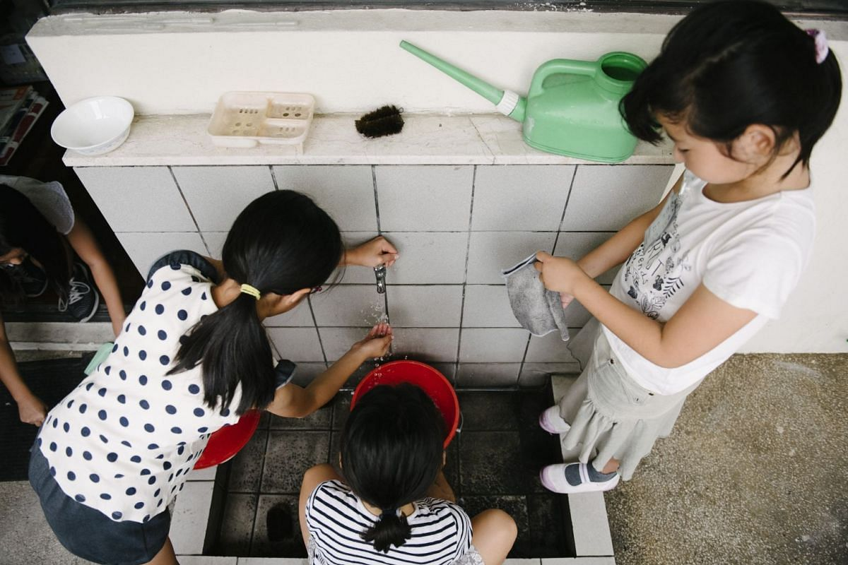 Grade 5 pupils at The Japanese School's Changi campus doing their routine morning cleaning (above).